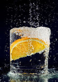 Scheibe orange im glas mit wasser auf tiefes blau fallen