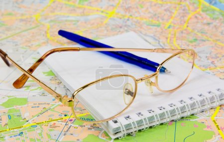 Photo for Qlasses, notebook and the pen lying on the map - Royalty Free Image