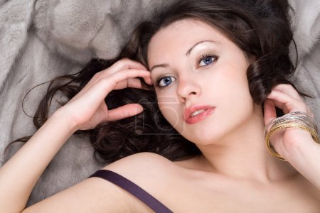 Sensual young woman lying on grey fur coat