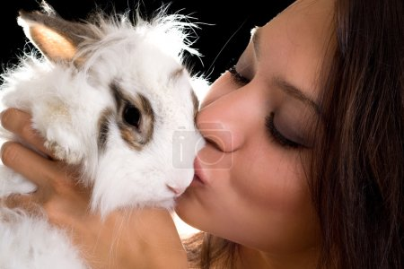Photo for Portrait of young woman kissing little rabbit. Isolated on black - Royalty Free Image