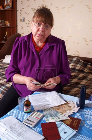 Photo for An elderly woman pays the bills - Royalty Free Image