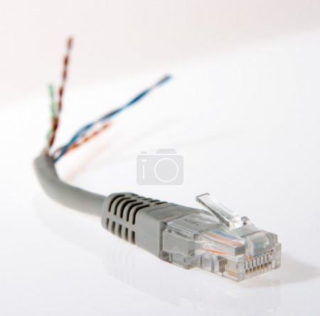 Torn network cable closeup, patch cable on the whi...