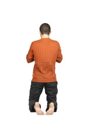 Photo pour Un homme agenouillé avec le dos, isolé sur fond blanc - image libre de droit