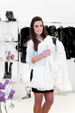 Photo pour Jeune femme essaie sur un manteau de fourrure de vison blanc - image libre de droit