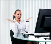 Happy businesswoman sits at the computer