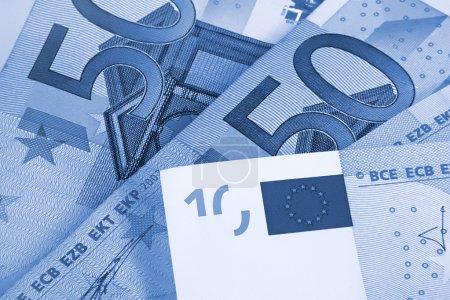 Photo pour Fragment de cinquante et dix euros d'argent, fond abstrait bleu - image libre de droit