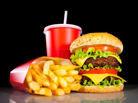 Photo for Tasty hamburger and french fries on a dark background - Royalty Free Image