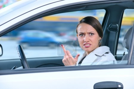 Angry woman in a car is showing her middle finger