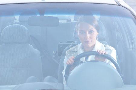 Beautiful woman is sitting in her car