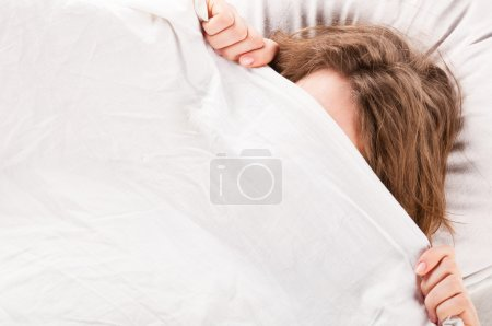 Photo for Angry woman is lying in bed under blanket and doesn't want to wake up - Royalty Free Image