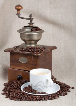 Antique coffee grinder, fried beans and cup