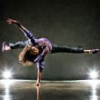 Young woman dancer. On wall background....