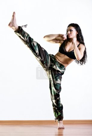 Photo for Young woman in military clothes kicking. - Royalty Free Image