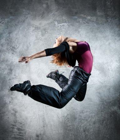 Photo pour Jeune femme danseuse sautant. Sur fond de mur . - image libre de droit