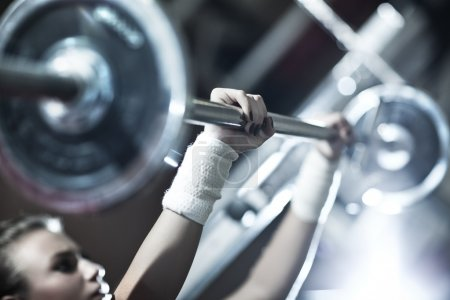 Photo for Young woman weight training. Focus on hand. - Royalty Free Image