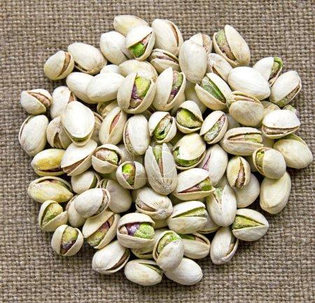 Delicious pistachios on sackcloth background