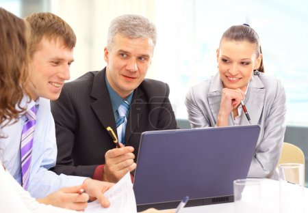 Small business team in the office in front of a whiteboard discussing a pro