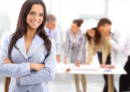 Portrait of a charismatic woman at a meeting while her team working in the