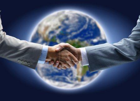 Photo pour Poignée de main avec carte du monde en arrière-plan - image libre de droit