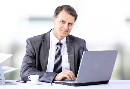 Photo for Businessman sitting at desk and working with laptop computer. - Royalty Free Image