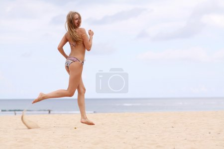 Photo pour Femme heureuse en bikini marche sur une plage - image libre de droit