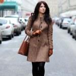 Beautiful young woman walking on the street...