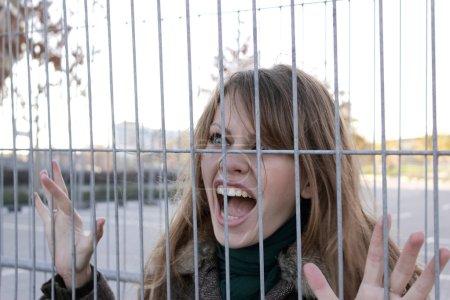 Photo pour Fille pleure très fort derrière les barreaux de fer - image libre de droit