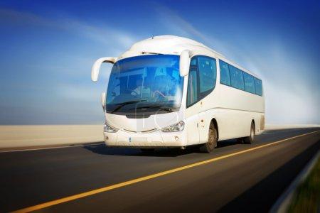 Photo pour Bus touristique blanc en mouvement sur l'autoroute et fond flou - image libre de droit