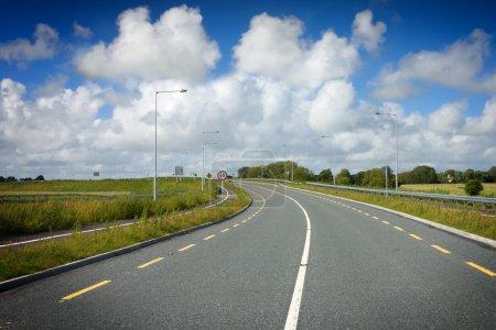 Photo pour Nouvelle autoroute avec marquage routier et ciel bleu avec nuages - image libre de droit