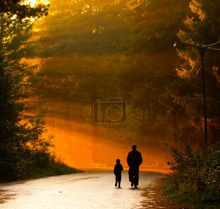 Photo for Father and son walking in the sunlight - Royalty Free Image