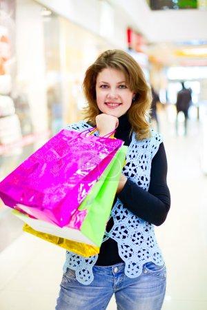Photo pour Belle jeune femme avec des sacs à provisions dans la boutique - image libre de droit