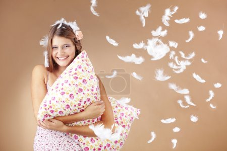 Photo for Beautiful teenage girl holding a pillow studio shot - Royalty Free Image