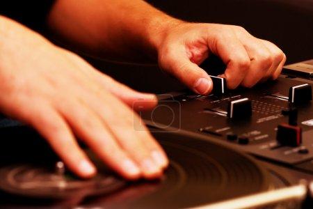 Photo pour Mains de disc jockey jouant de la musique sur le plateau tournant et le contrôleur de mixage haut de gamme - image libre de droit