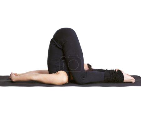 Yoga excercising karnapidasana