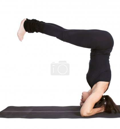 Photo pour Full-length portrait of beautiful woman working out yoga excercise salamba sirsasana (supported head stand) on fitness mat - image libre de droit