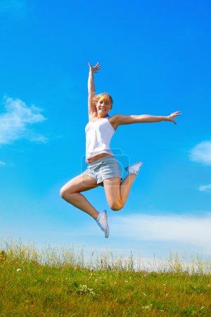 Photo pour Jeune fille heureuse sautant sur prairie ensoleillée - image libre de droit