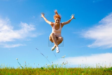 Photo for Young happy girl jumping on sunny meadow - Royalty Free Image