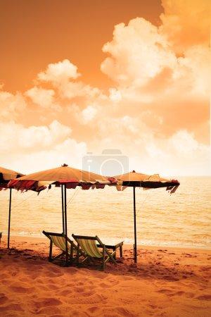 Photo pour Chaises et parasols à une plage de sable sépia tonique - image libre de droit