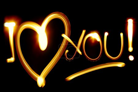 Photo for I LOVE YOU phrase created by light over black background - Royalty Free Image