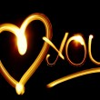 I LOVE YOU phrase created by light over black back...