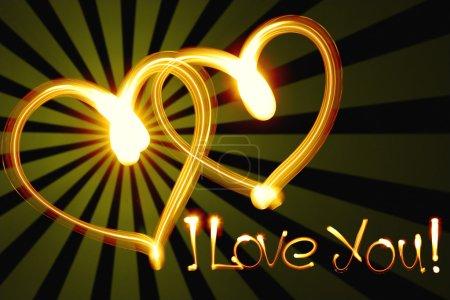 Photo pour Deux cœurs créés par la lumière sur fond noir - image libre de droit