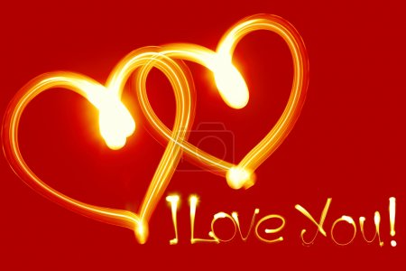 Two hearts created by light over red background