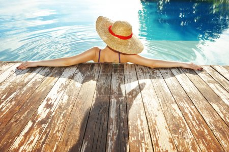 Photo for Woman in hat relaxing at the pool - Royalty Free Image