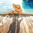 Woman in hat relaxing at the pool...