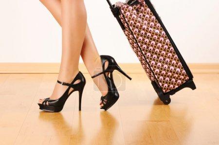 Photo pour Jambes de femme et valise de voyage - image libre de droit