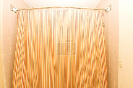 Bath tub behind striped colourful curtain