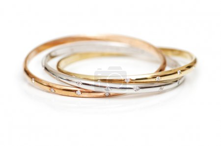 Three gold bracelets isolated on the white...
