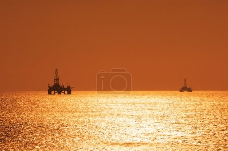 Two offshore oil rigs during sunset in Caspian sea...
