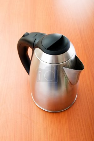 Shiny tea kettle on the wooden table