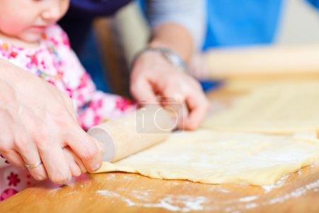 Closeup of family baking pie